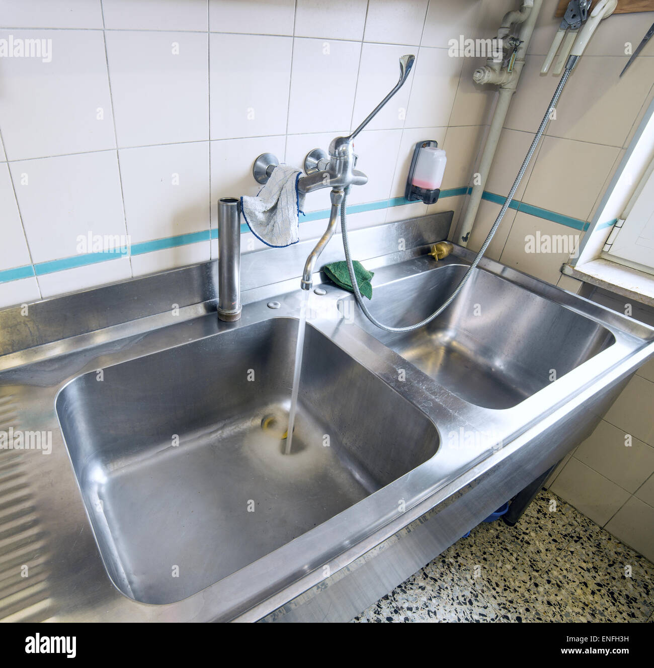 sink stainless steel industrial kitchen with open tap Stock Photo