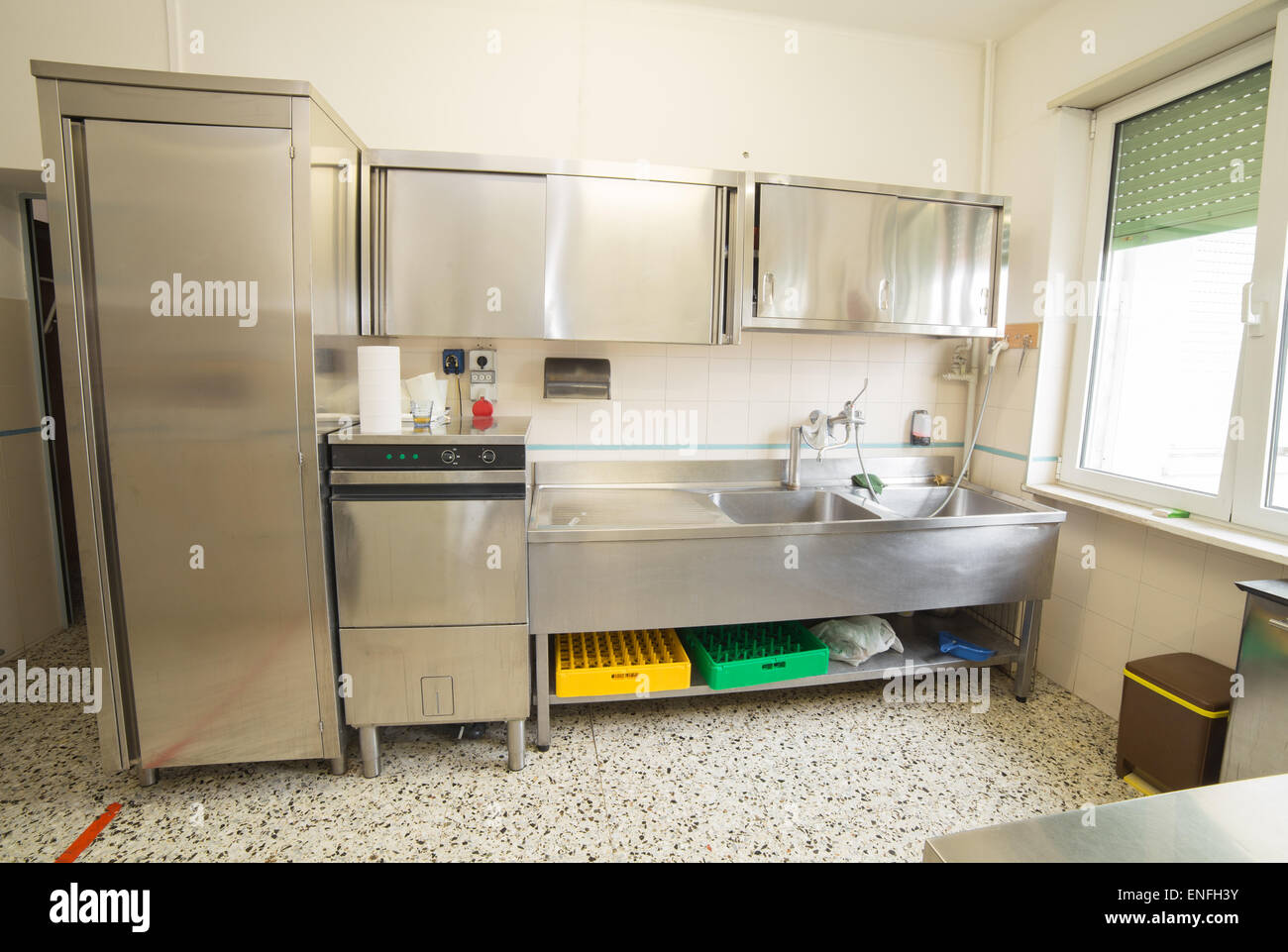 large industrial kitchen with refrigerator, dishwasher and sink all stainless steel Stock Photo