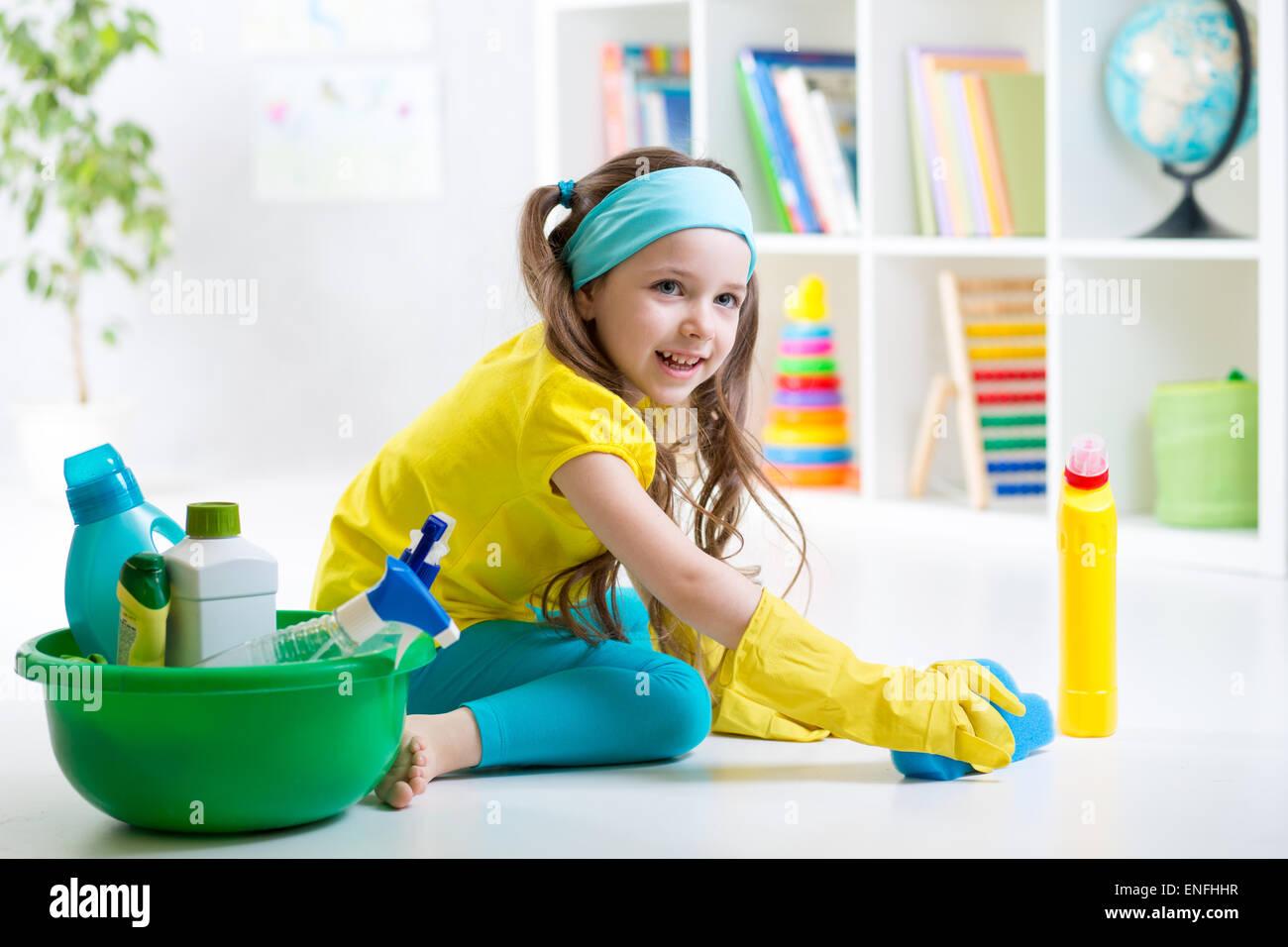 Cute kid little girl cleanses a floor in children room - Stock Image