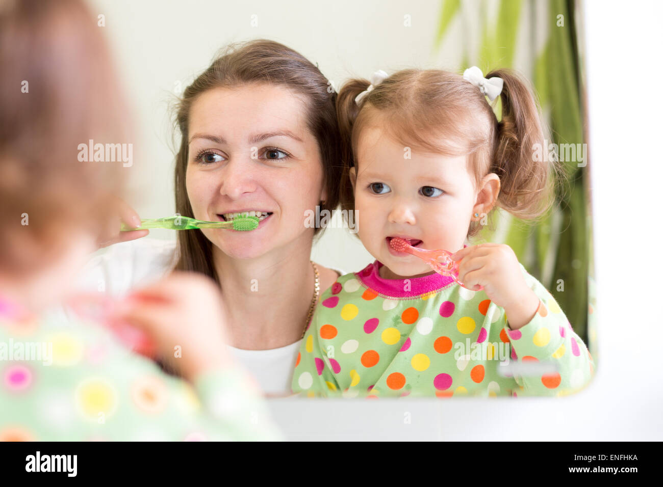 mother teaching daughter child teeth brushing in bathroom - Stock Image