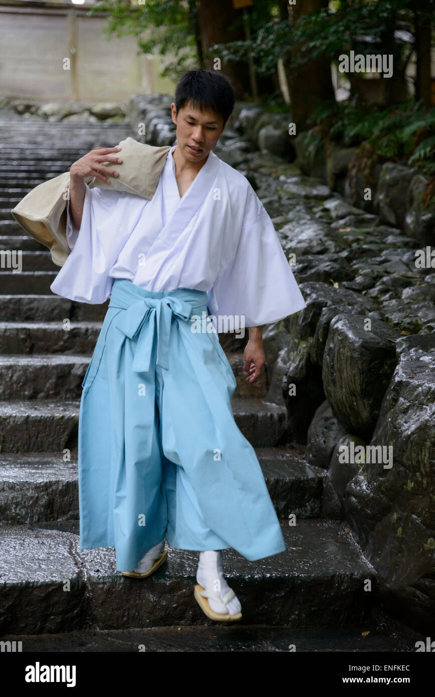 Japanese Shinto priest in traditional costume carrying a heavy bag down steps at The Grand Shrine, Ise (Ise Jingu), - Stock Image