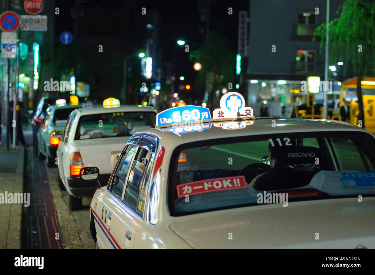 Atmosphere of the night in Japan: taxis wait for customers in a Japanese city entertainment district. Taxi rank, - Stock Image