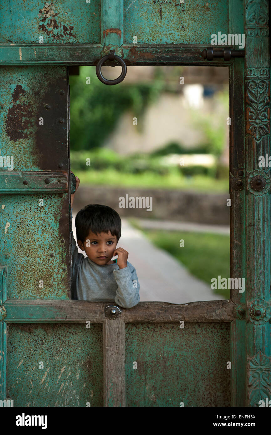 Little boy at a gate of the City Palace, Udaipur, Rajasthan, India - Stock Image