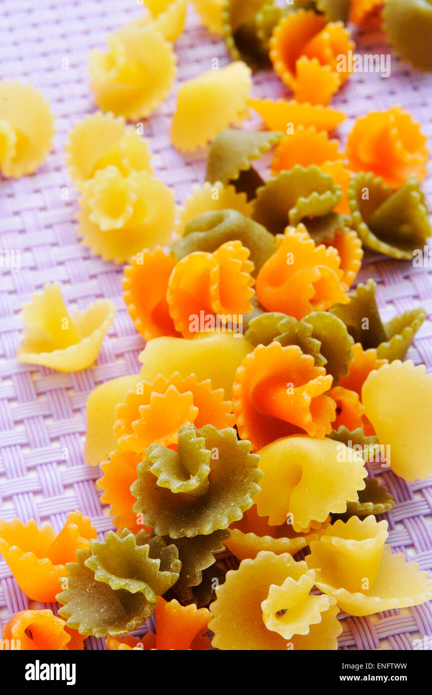 a pile of uncooked vegetables short pasta on a purple tablecloth - Stock Image