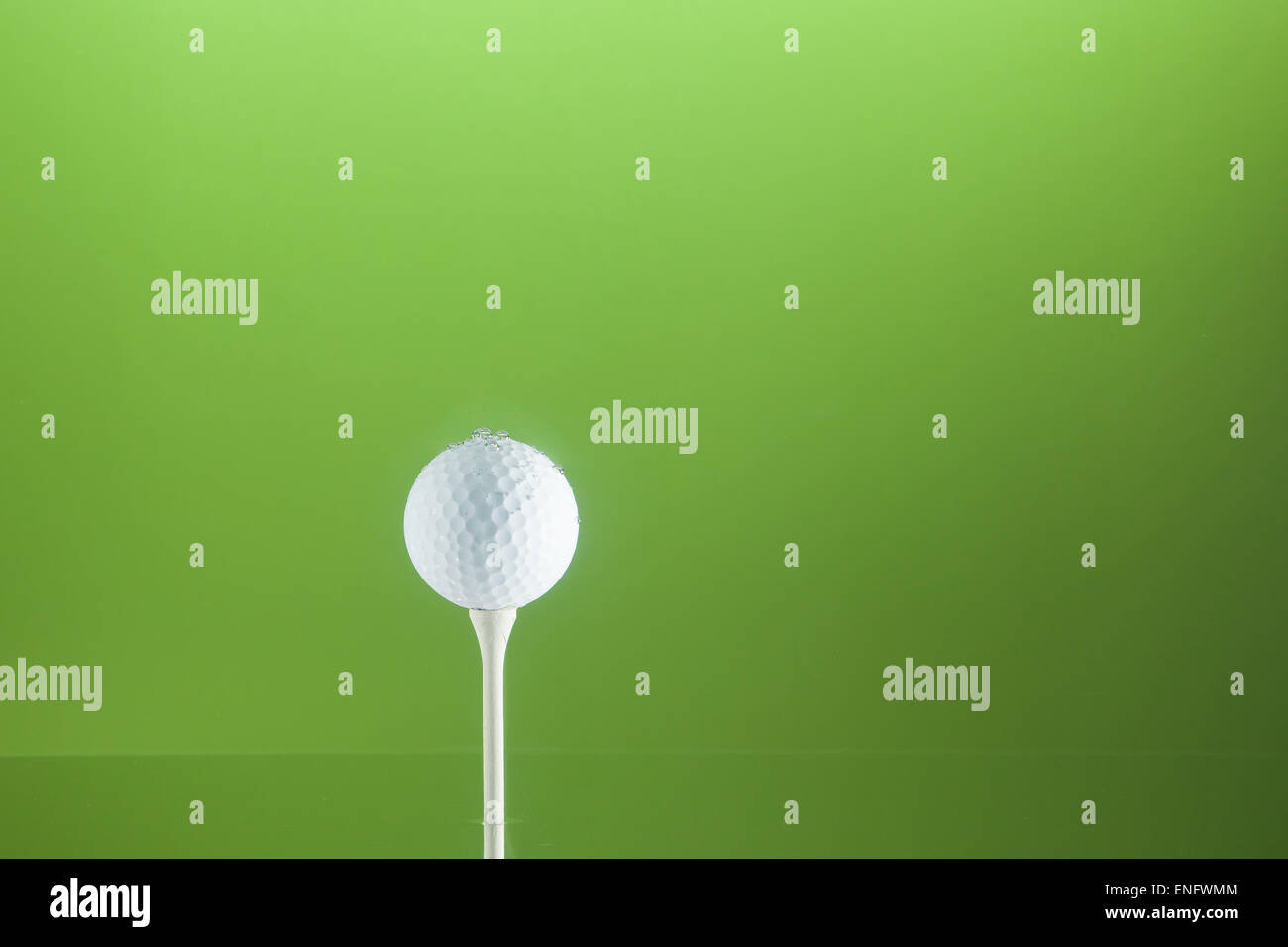 Golfball on a peg in water. - Stock Image