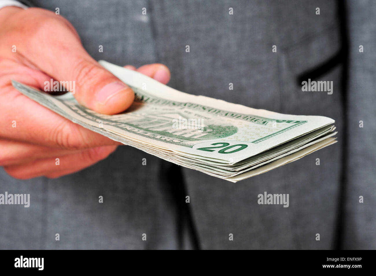 a man wearing a suit with a wad of dollars in his hand - Stock Image