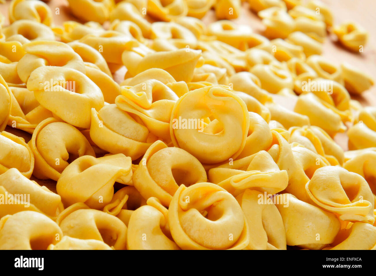 closeup of a pile of uncooked tortellini on a wooden table - Stock Image