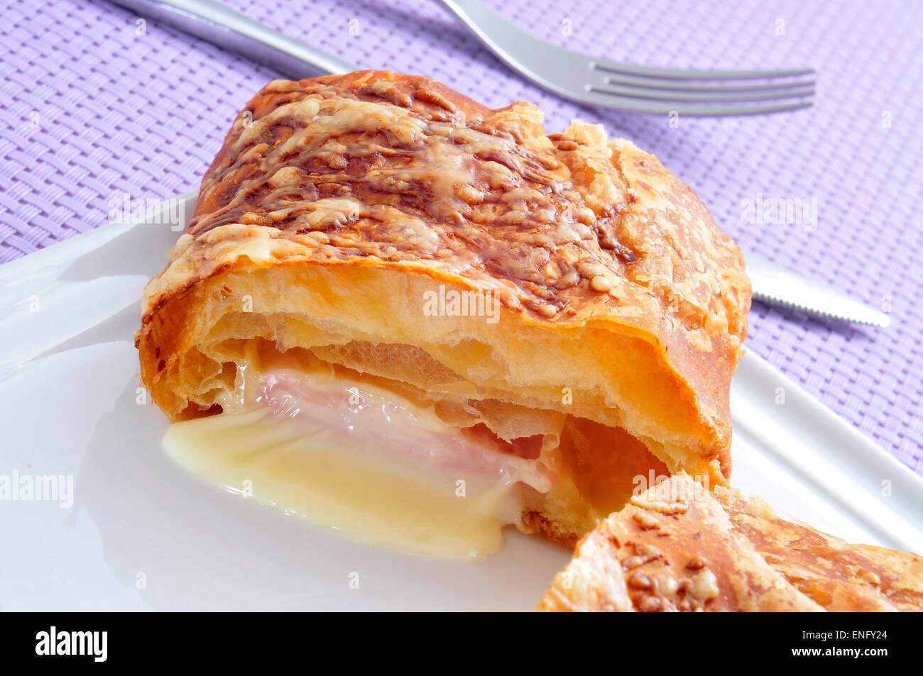 plate with a ham and cheese croissant on a set table with a purple tablecloth - Stock Image