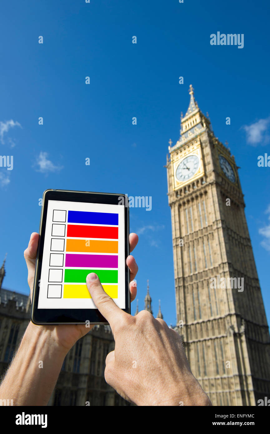 Finger of voter choosing candidates on digital tablet computer outside Big Ben Westminster Palace London under bright - Stock Image