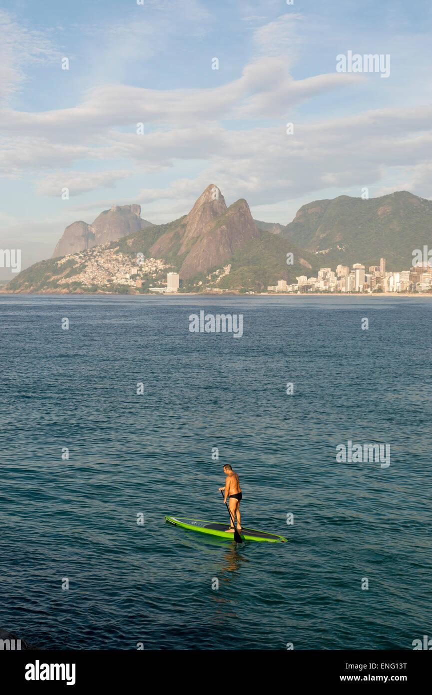 RIO DE JANEIRO, BRAZIL - MARCH 22, 2015: Brazilian stand up paddler enjoys calm seas near the Arpoador section of - Stock Image