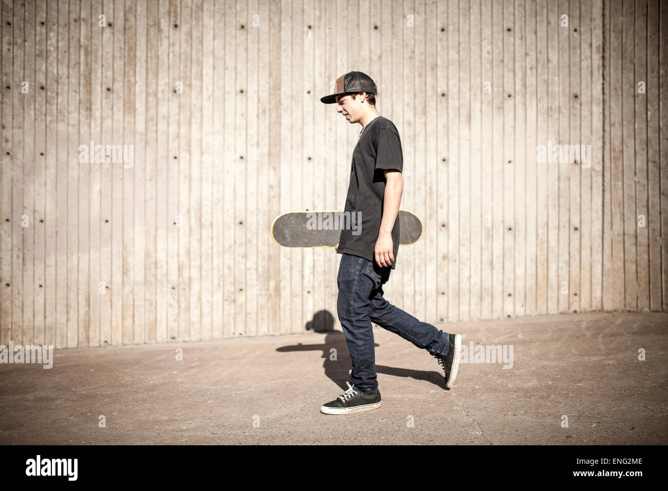 Caucasian man carrying skateboard near wooden wall - Stock Image