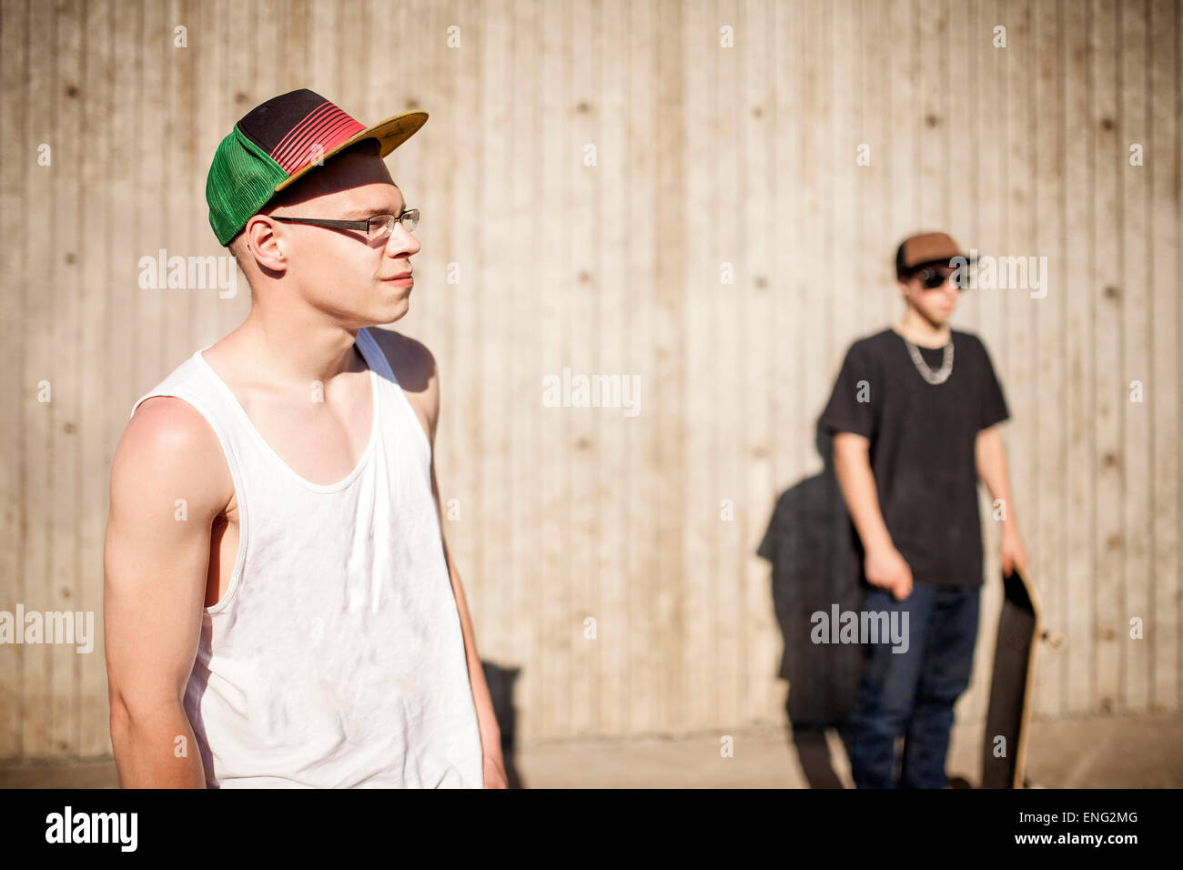 Caucasian men with skateboards near wooden wall - Stock Image