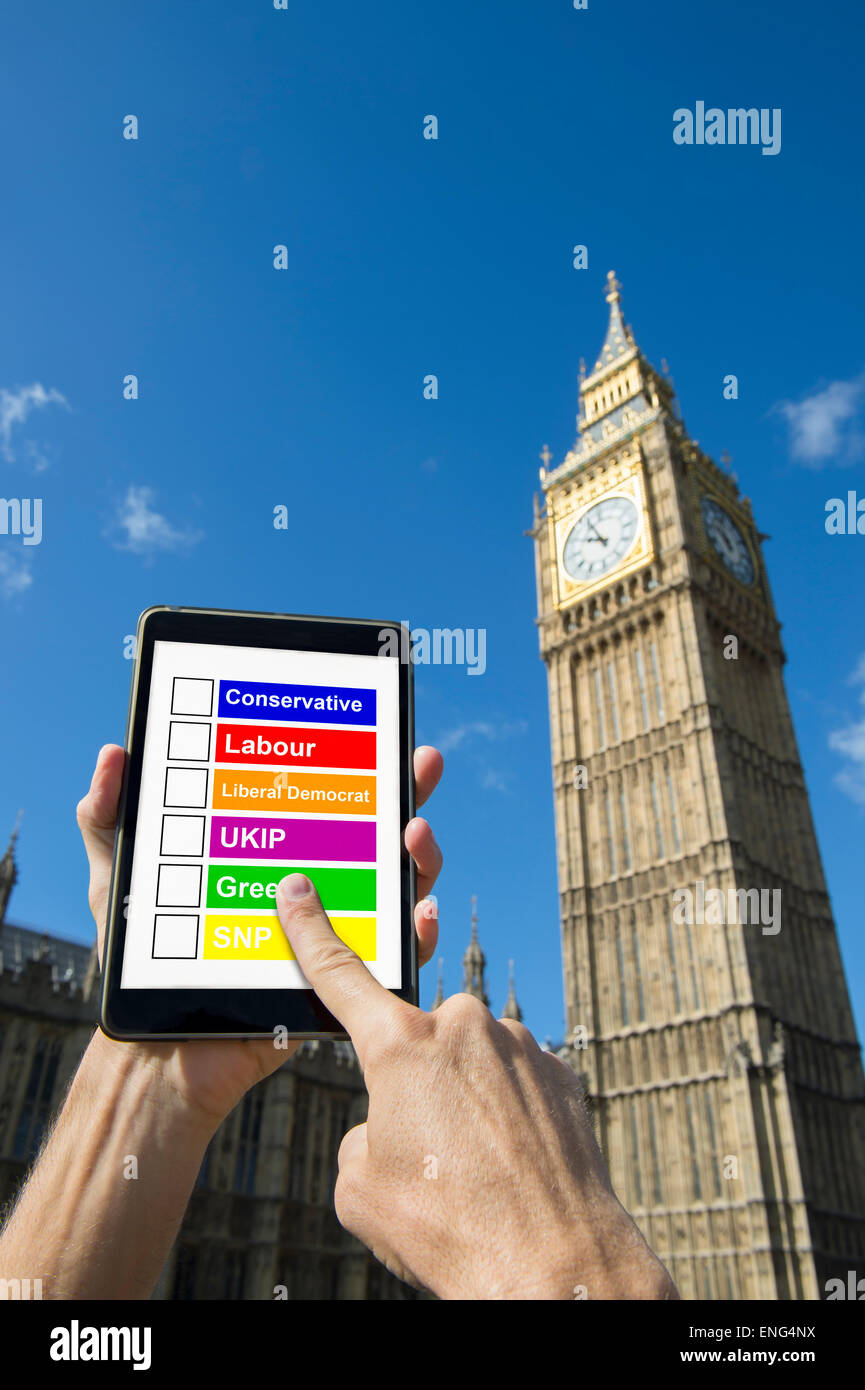 LONDON, UK - APRIL 27, 2015: British voter selects from a list of political parties on a tablet in front of Westminster - Stock Image