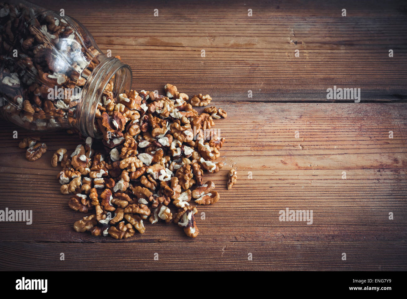 Walnut kernels and whole walnuts on rustic old wooden table glass jar Stock Photo