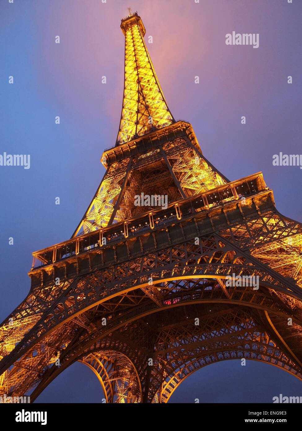 The Eiffel tower in Paris, France, illuminated with the top in the clouds mist fog - Stock Image