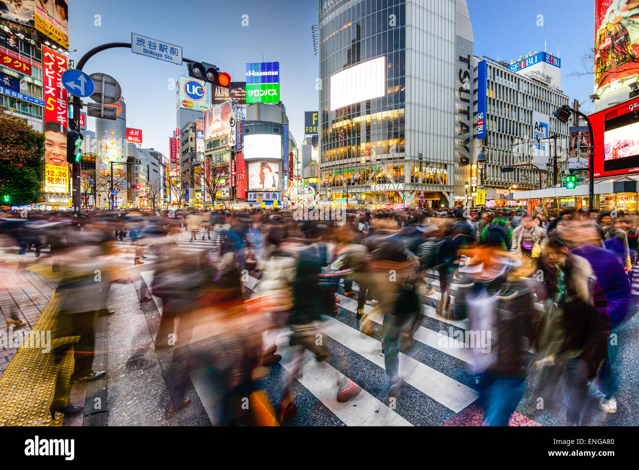 Pedestrians walk at Shibuya Crossing during the holiday season. The scramble crosswalk is one of the largest in - Stock Image