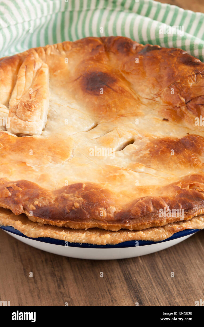 Home baked pie with a golden puff pastry crust baked in enamelware pie dish can be used for savory or sweet fillings - Stock Image