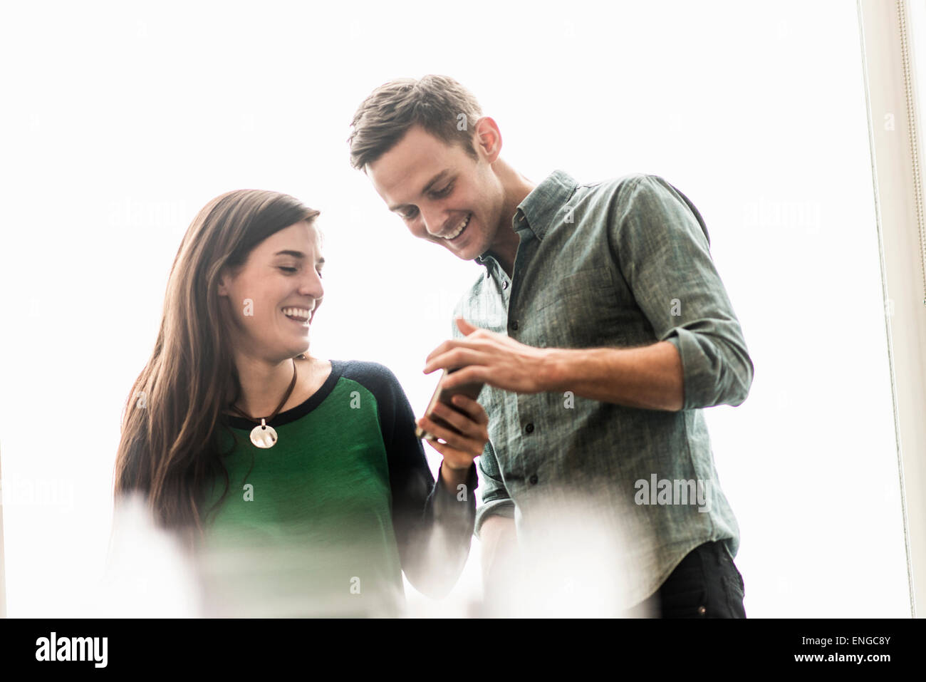 A man and woman talking in an office over coffee. - Stock Image
