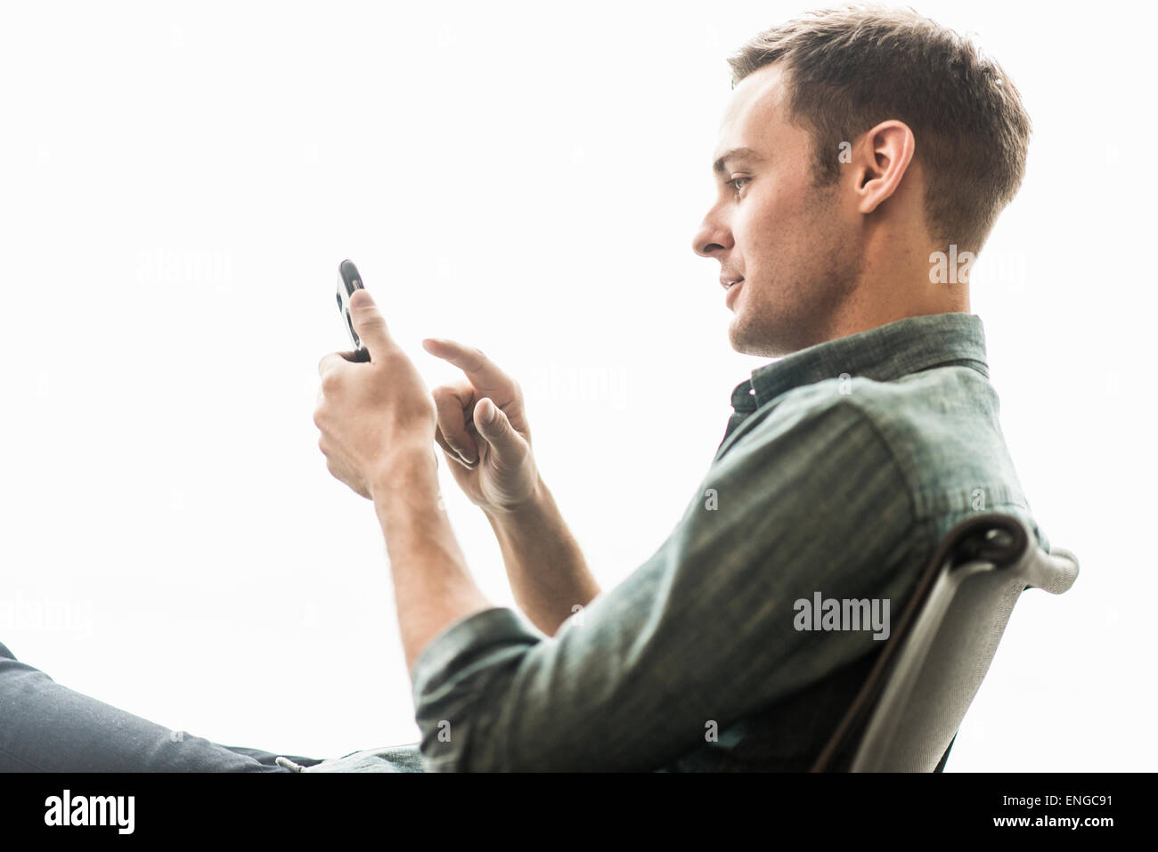 A man sitting checking his phone. - Stock Image
