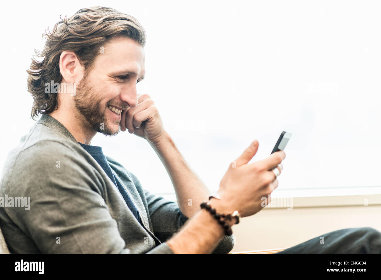 A bearded man sitting smiling and checking his phone. - Stock Image