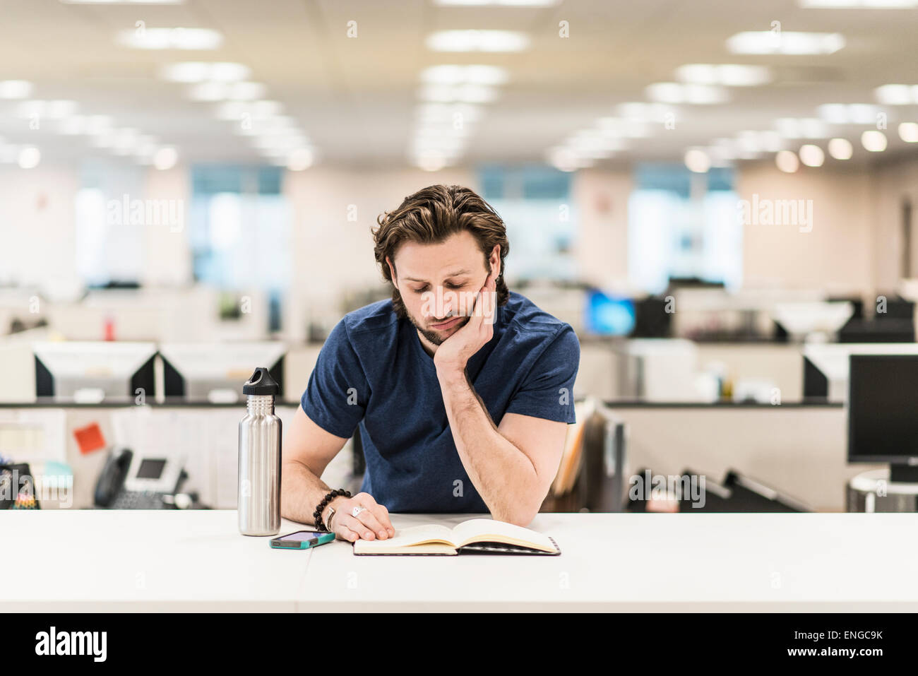 A man leaning on  his elbow and looking at an open book on an office desk. - Stock Image