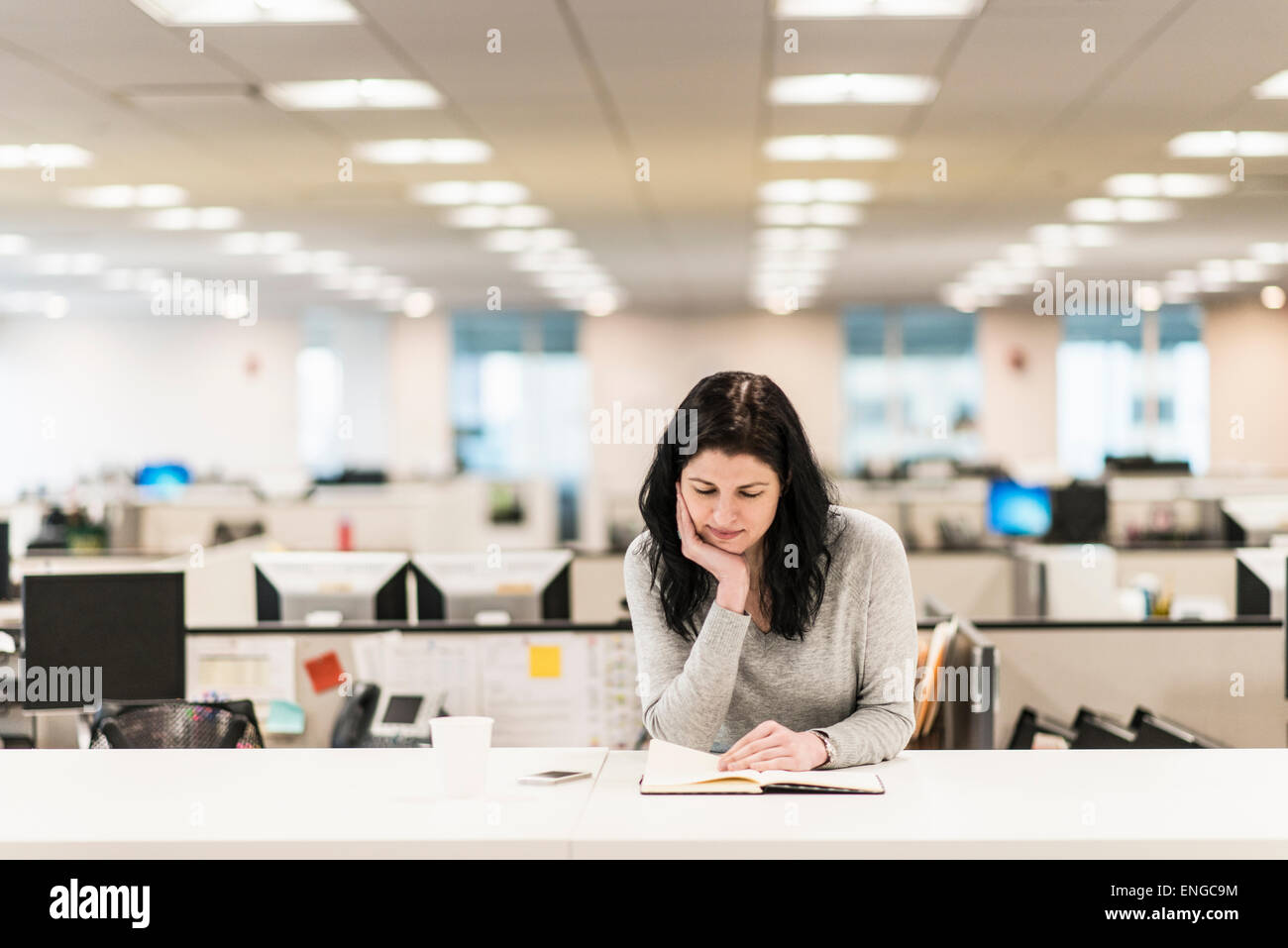 A woman seated with her hand resting on her chin, reading a book at a desk. - Stock Image