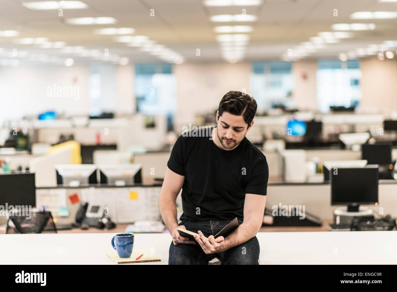 A man seated on a desk in an office looking at a book or diary. - Stock Image