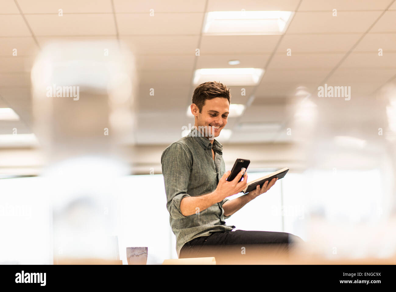 A young man seated looking at his smart phone, holding an open notebook. - Stock Image