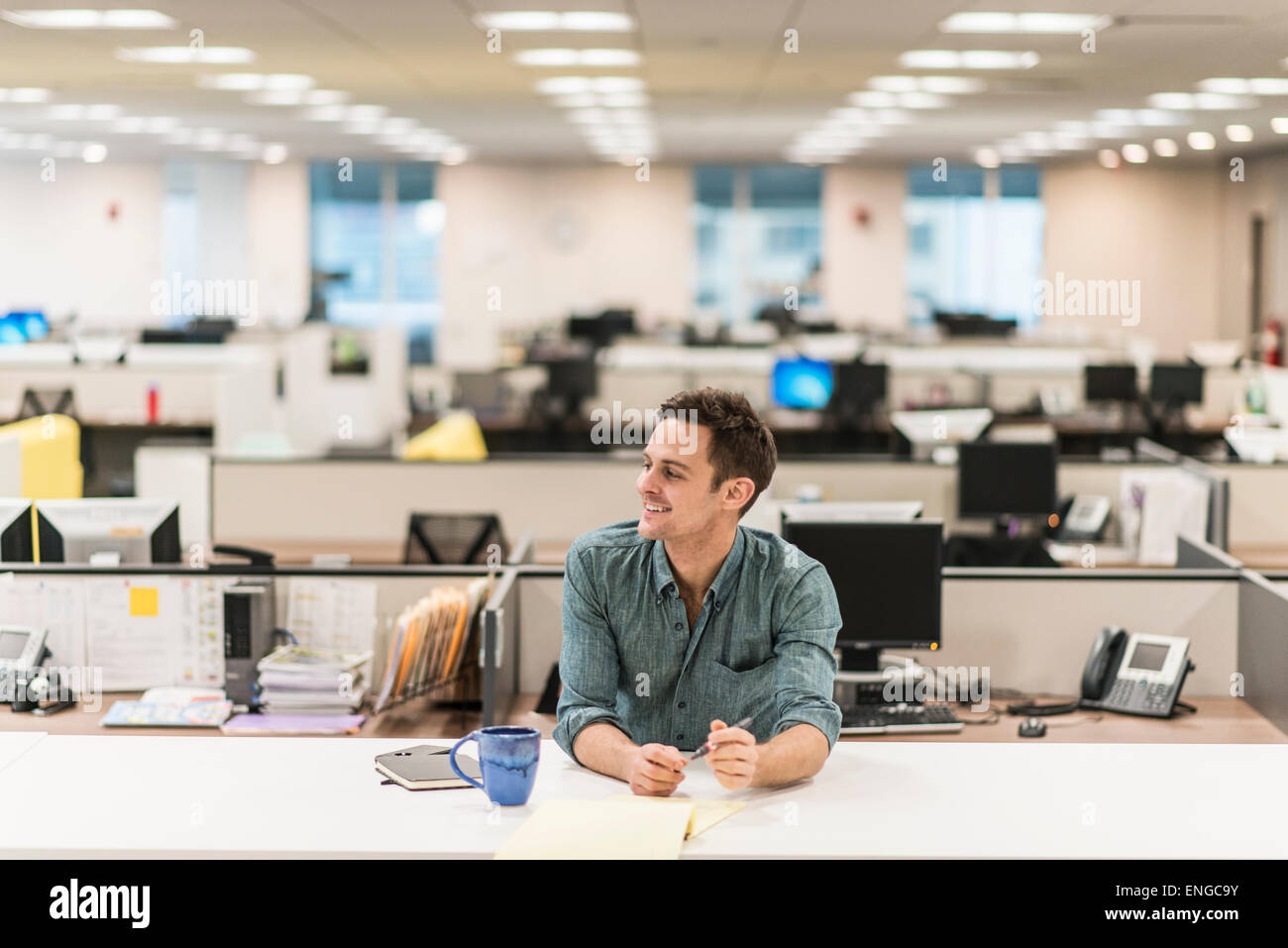 A young man seated at a desk in an office. - Stock Image