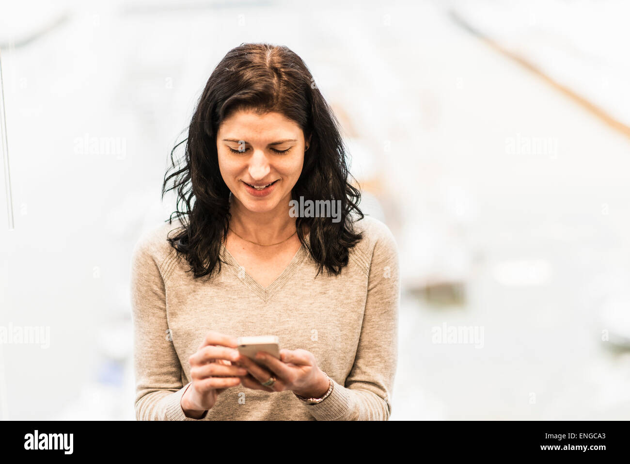 A business woman seated by a window using her smart phone. - Stock Image