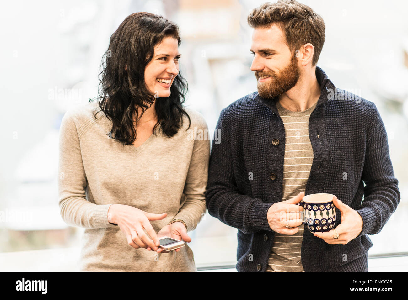A business woman seated by a window holding a smart phone, talking to a man with a coffee cup. - Stock Image