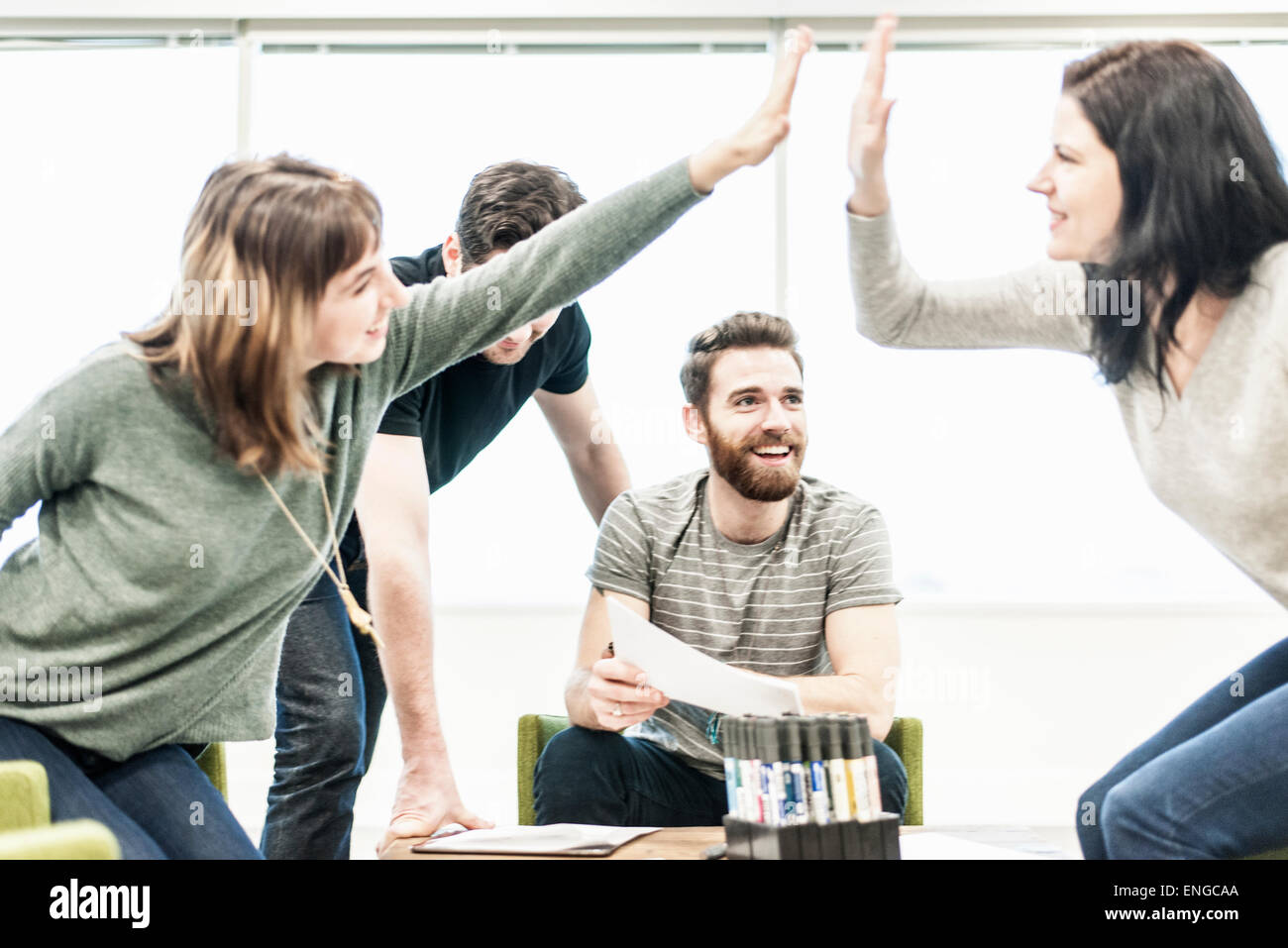 Four people seated at a table, colleagues at a planning meeting high fiveing each other. - Stock Image