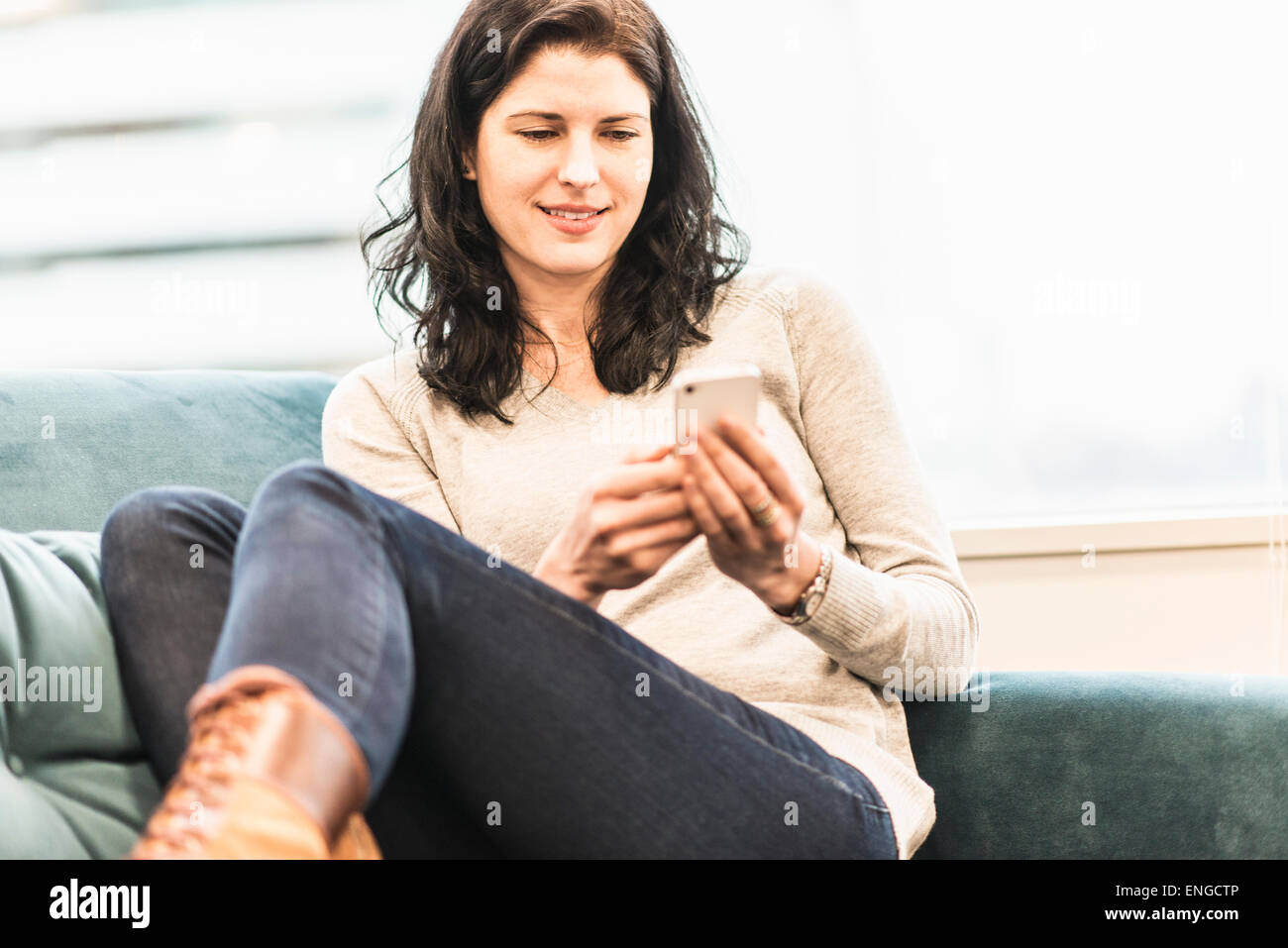 A woman seated with her feet up on a sofa, looking at her smart phone. - Stock Image