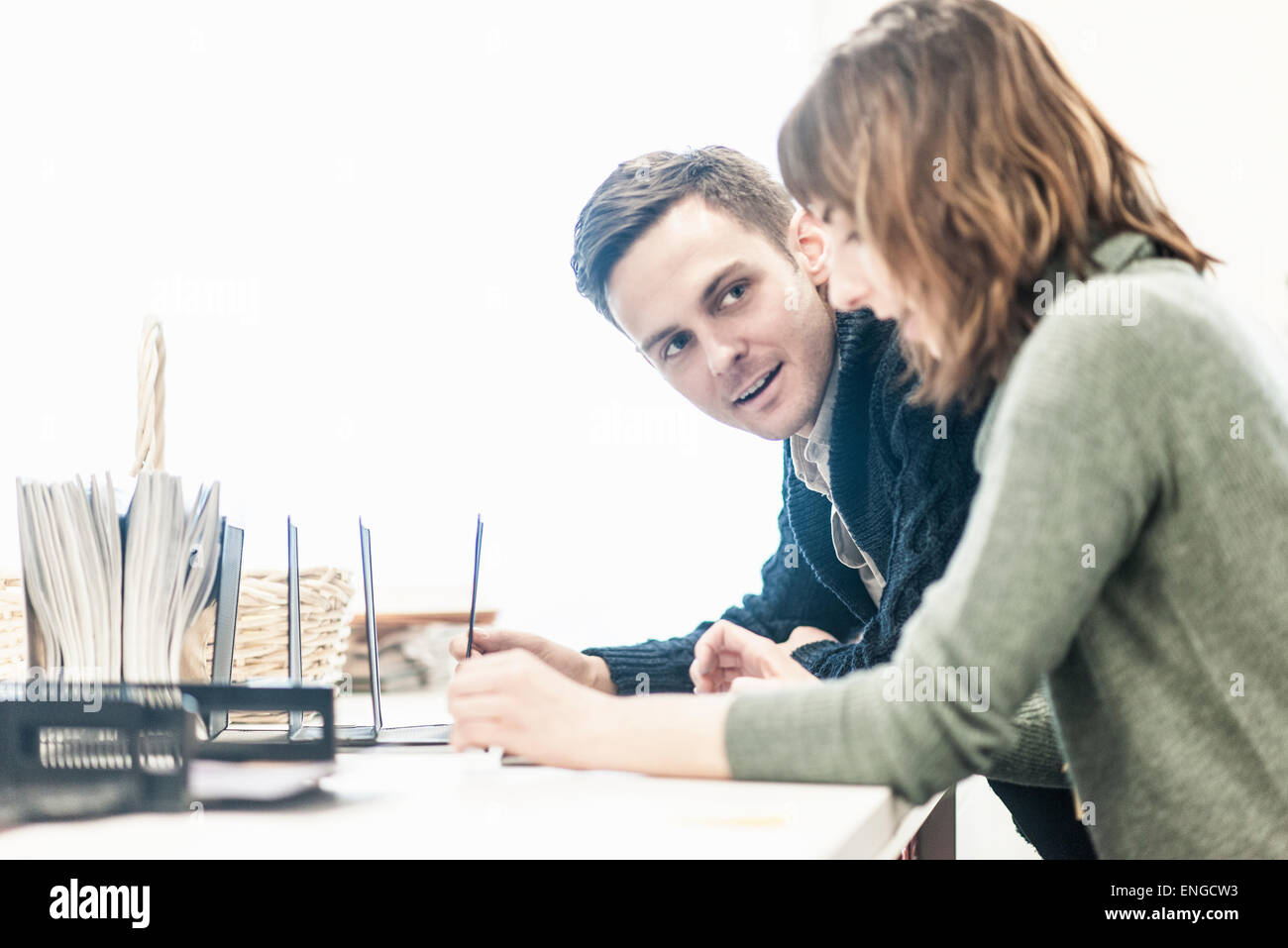 A man and a woman seated side by side talking at a desk in an office. - Stock Image