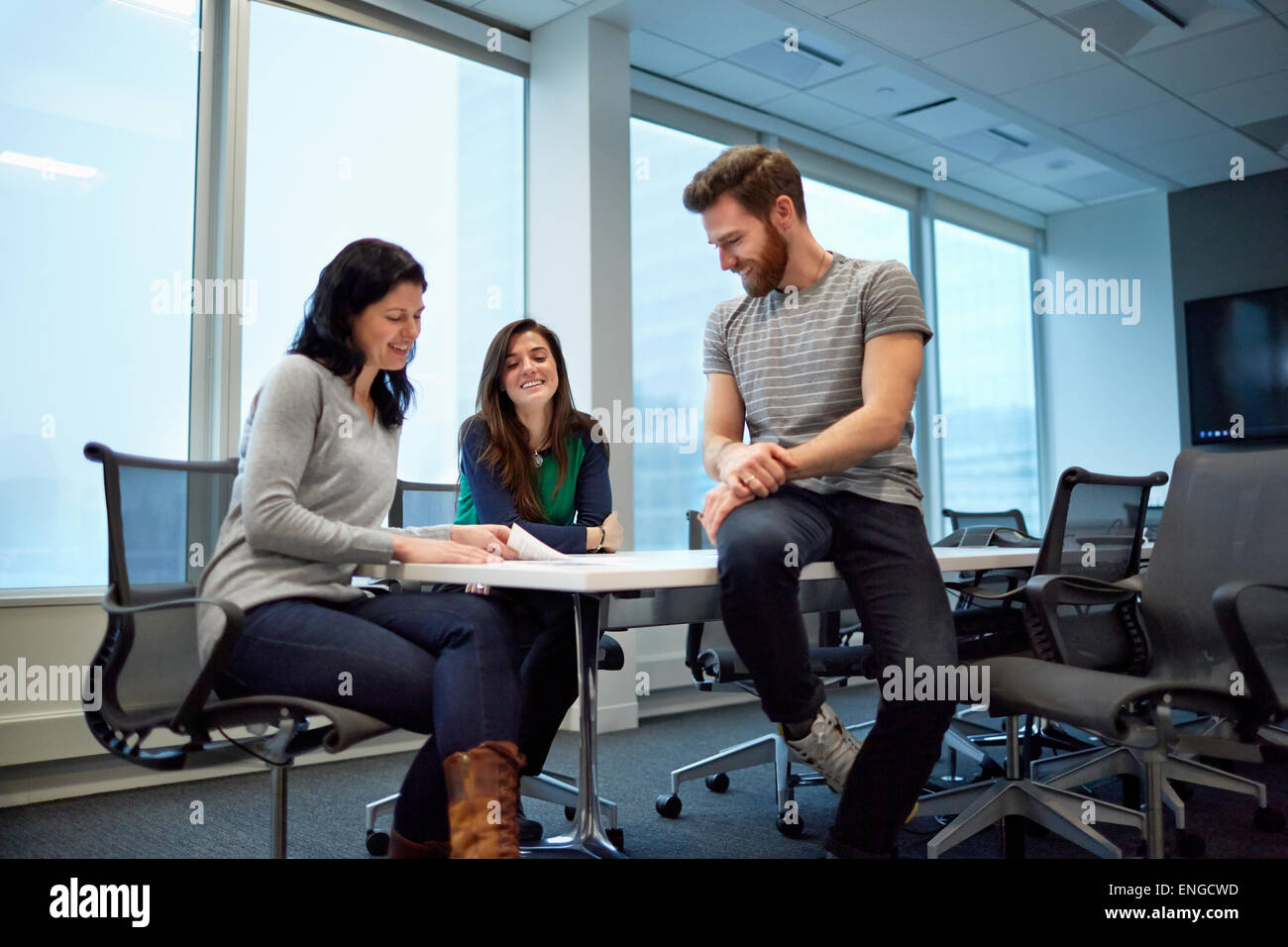 Three colleagues at a meeting Looking over proofs of printed pages and designs. A creative environment. - Stock Image