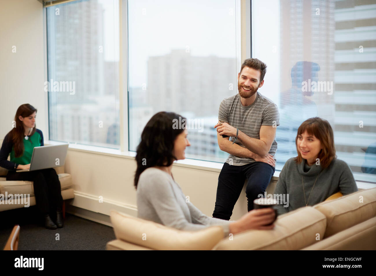 Three people by a window in an office, two women and a man. - Stock Image