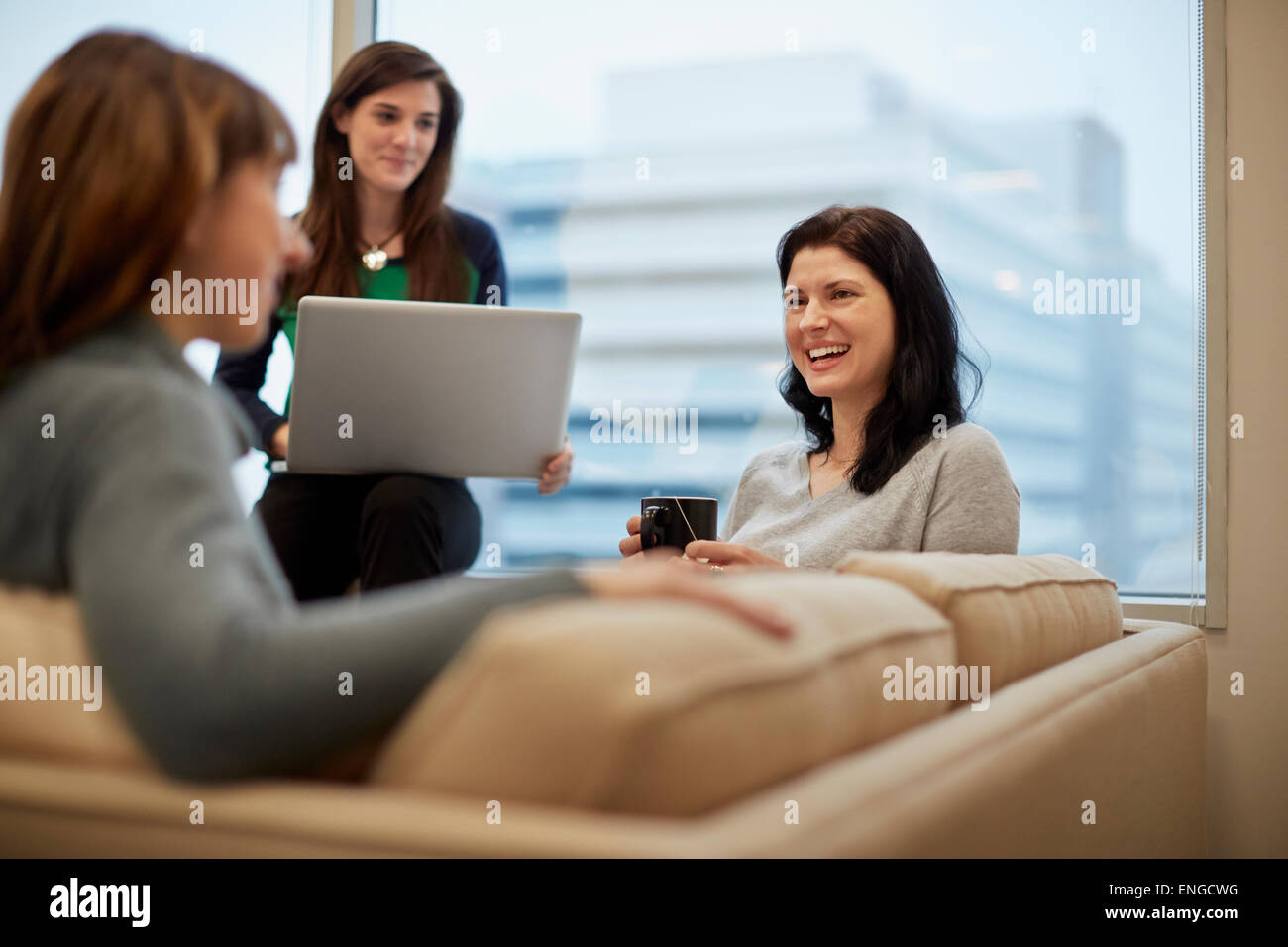 Three businesswomen by a window in an office, one holding a laptop. - Stock Image