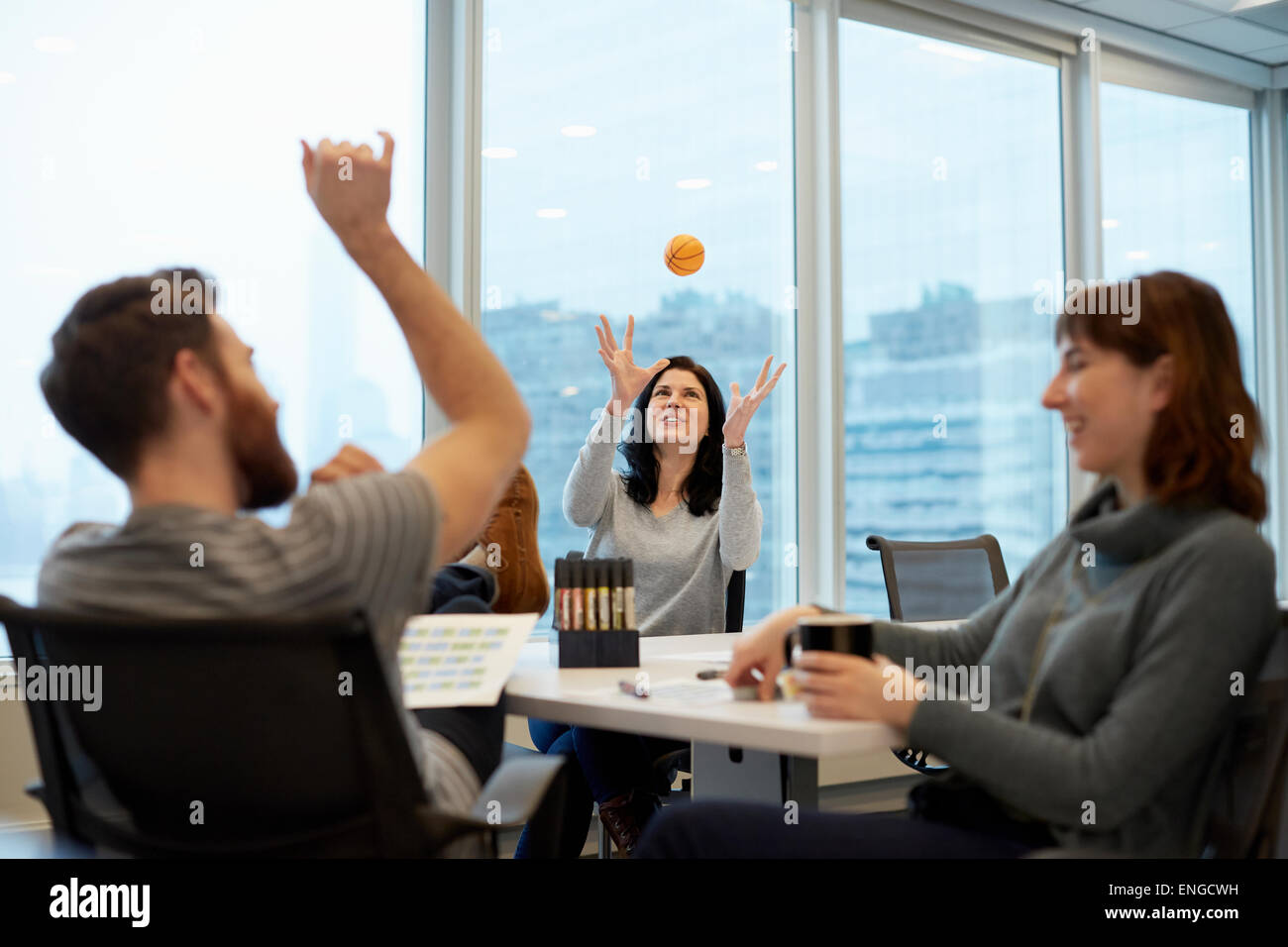 Three business people, two women and a man, reaching up to catch a ball. - Stock Image