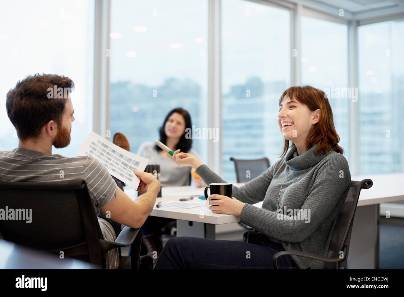 Three business people, two women and a man - Stock Image
