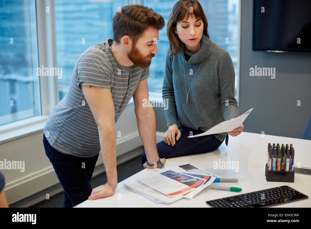 Two colleagues, a man and woman looking over printed pages on a desk. - Stock Image