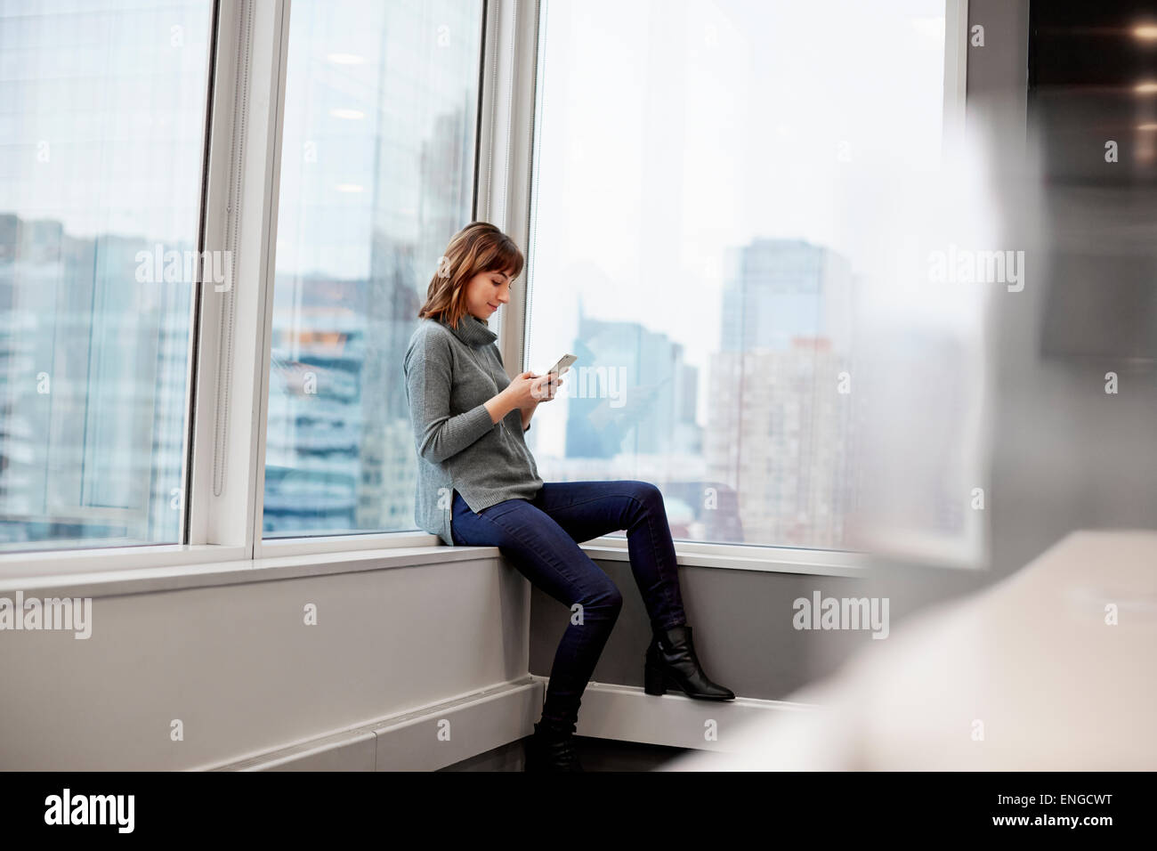 A woman sitting along, using a smart phone. - Stock Image