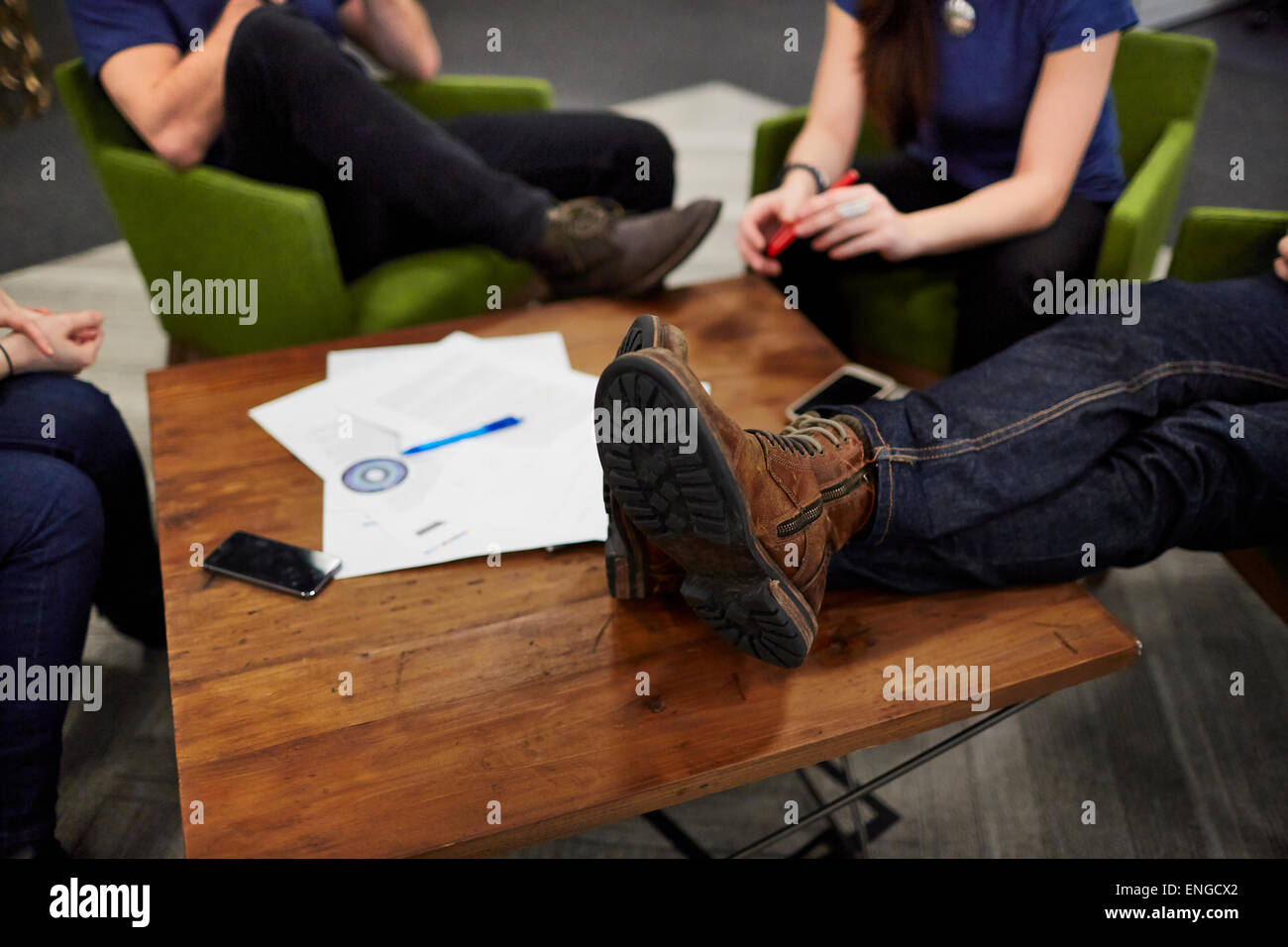 Overhead view of a meeting of four people seated around a low table. - Stock Image