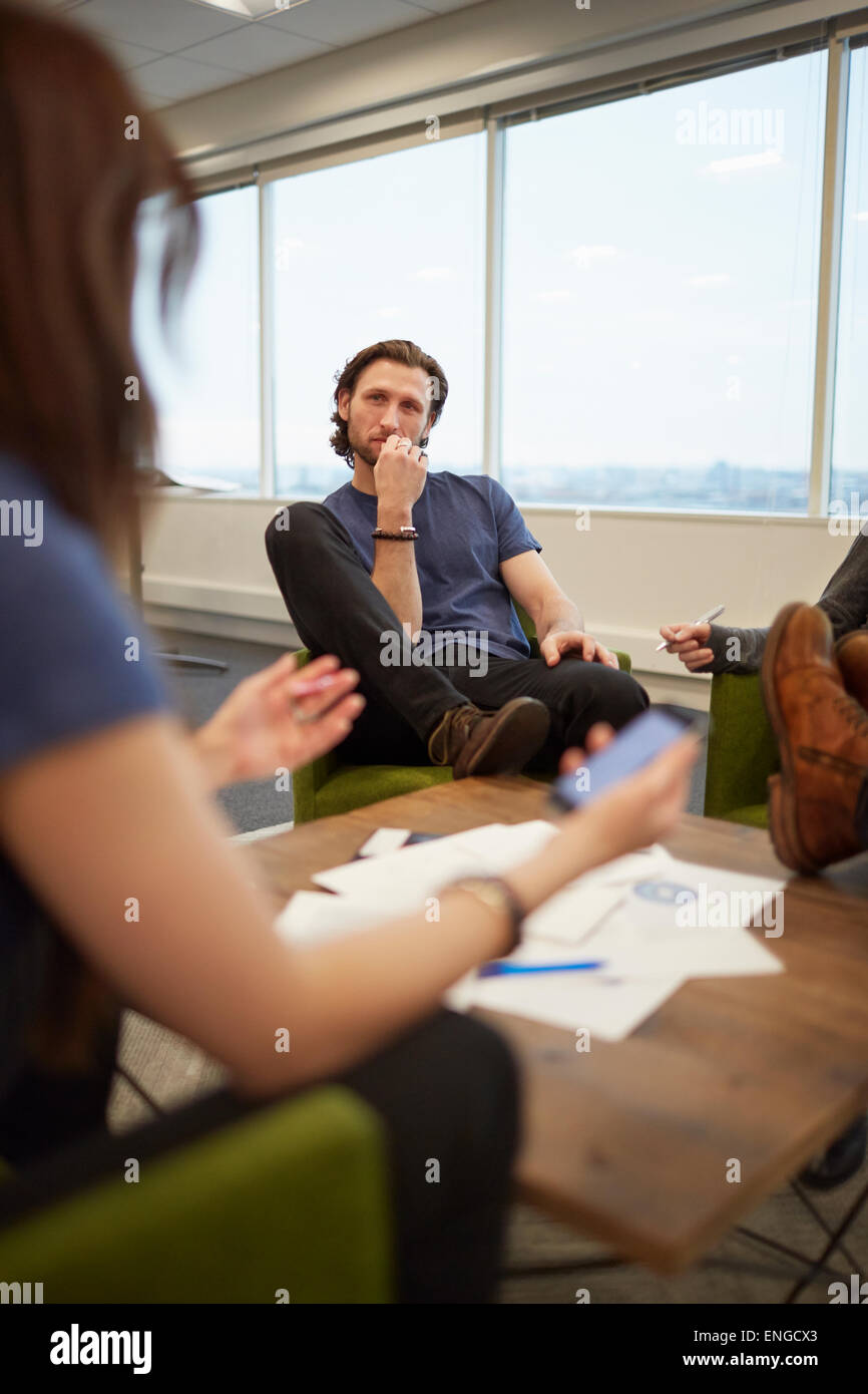A meeting of work colleagues, people around a low table. - Stock Image