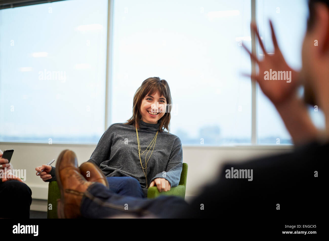 A woman seated in an office talking to someone with their feet up on the table. - Stock Image