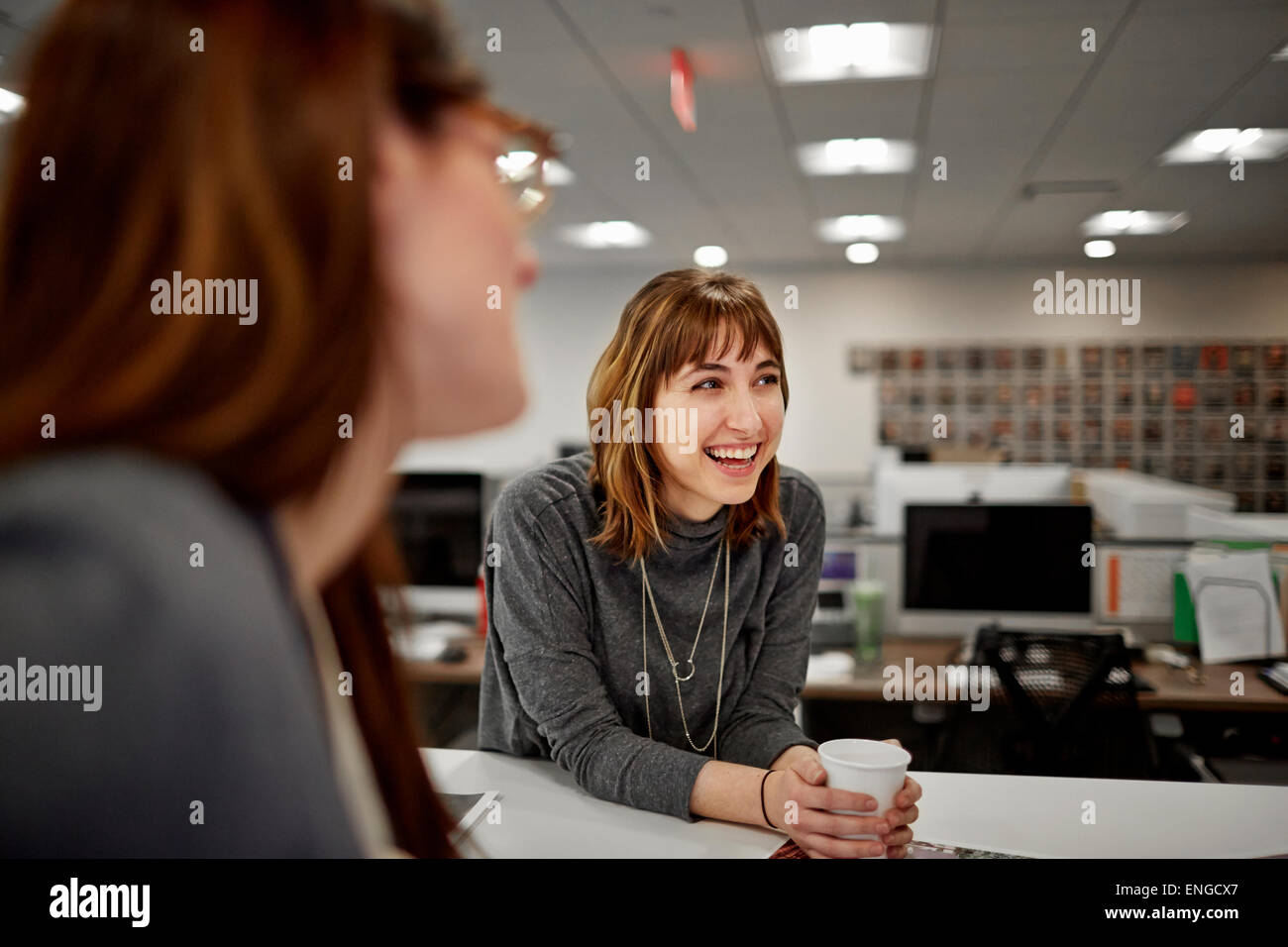 Two women seated in an office talking. - Stock Image