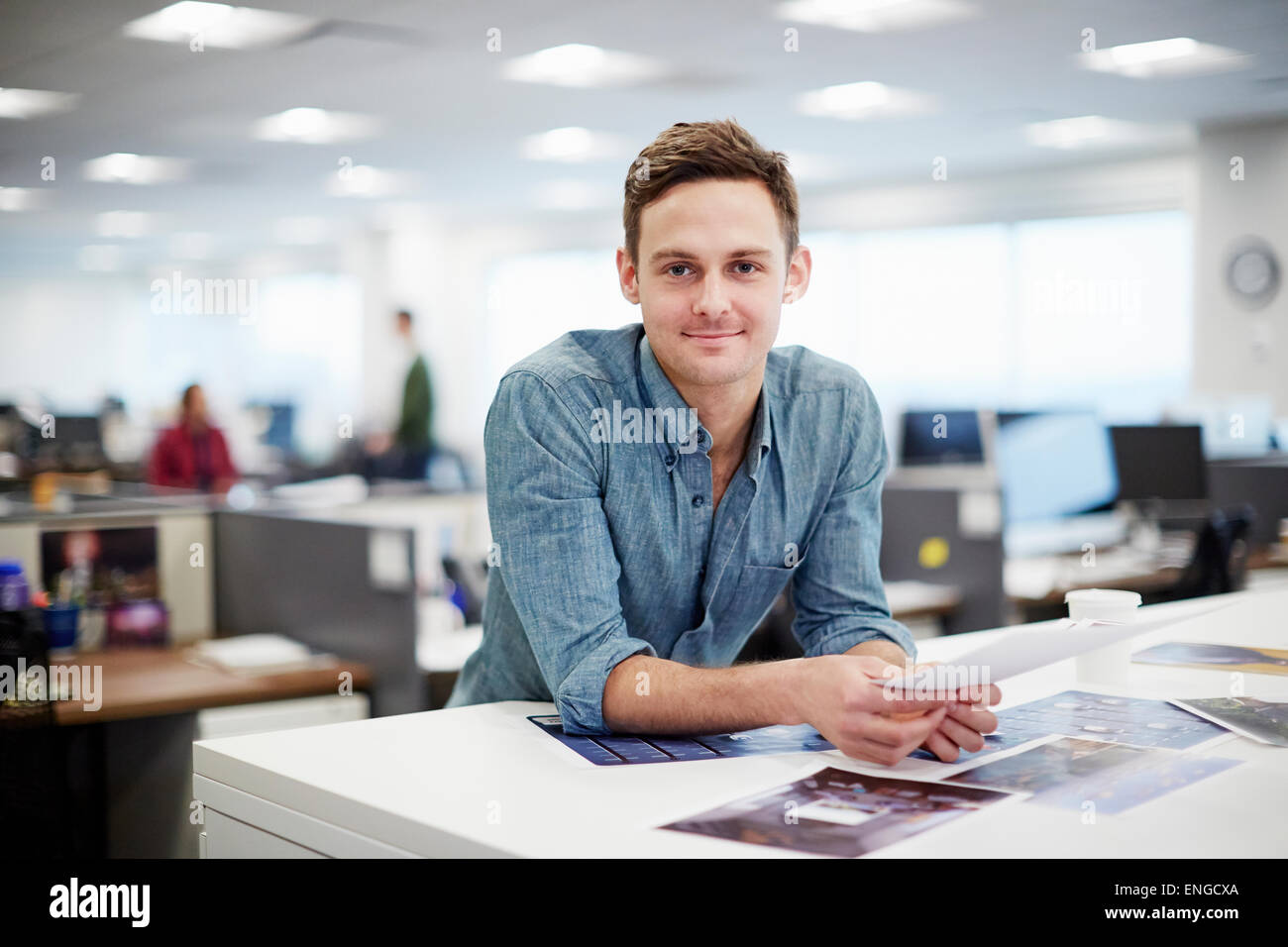 A man smiling and leaning forward on his desk. - Stock Image