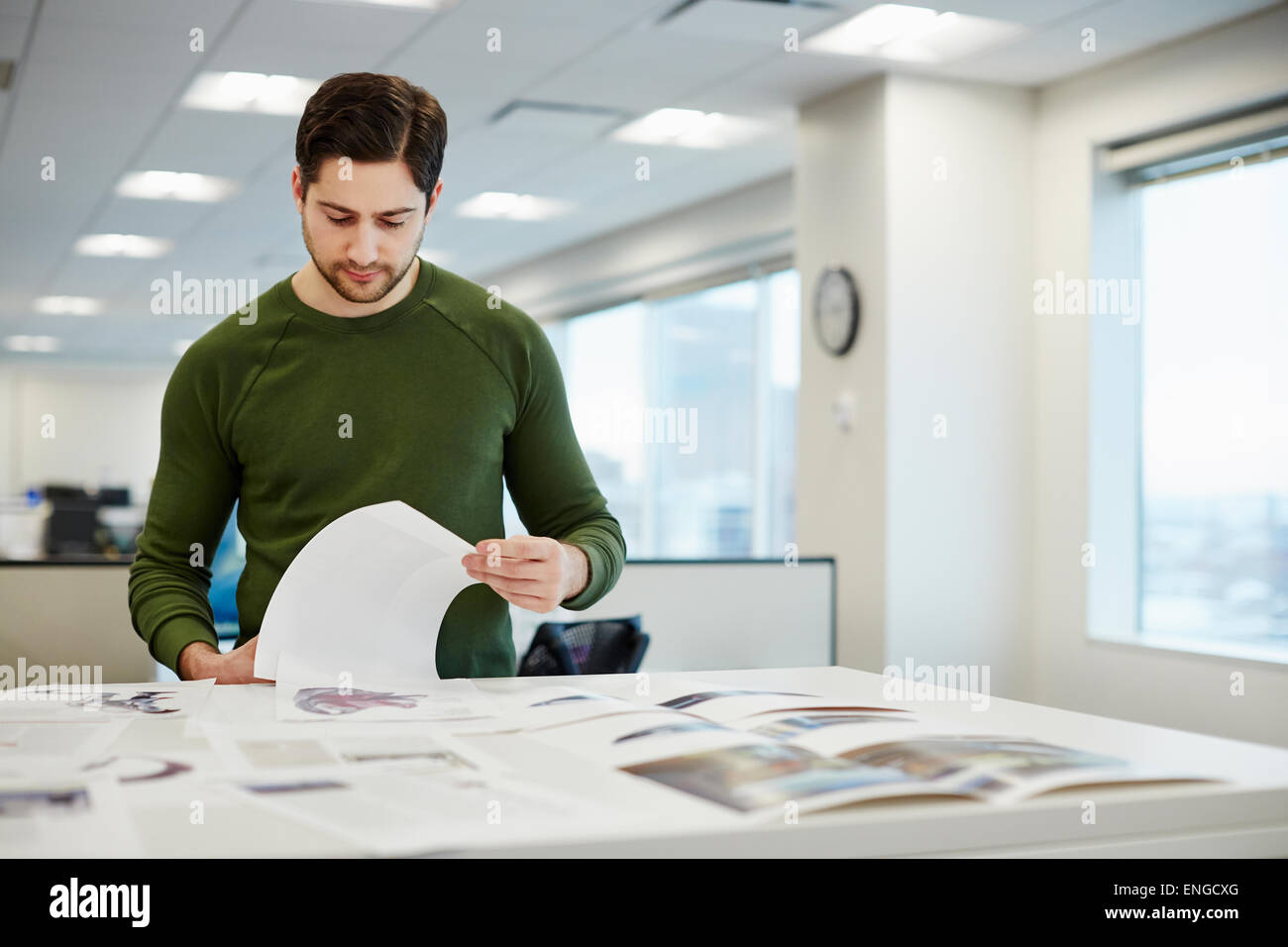 A man in an office checking proofs of printed pages. - Stock Image