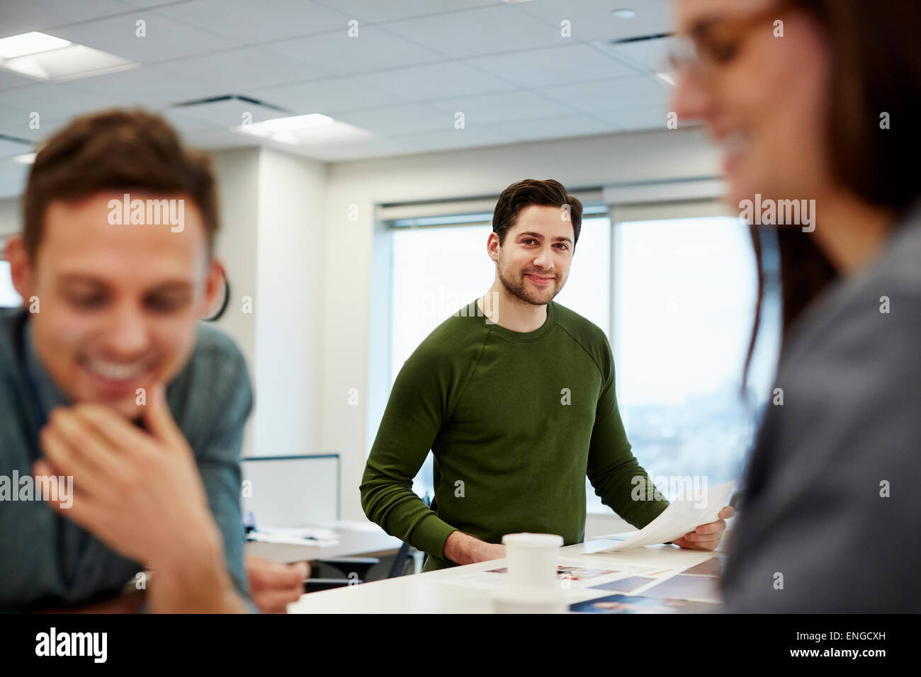 Three people in a large open plan office, two in the fore. - Stock Image