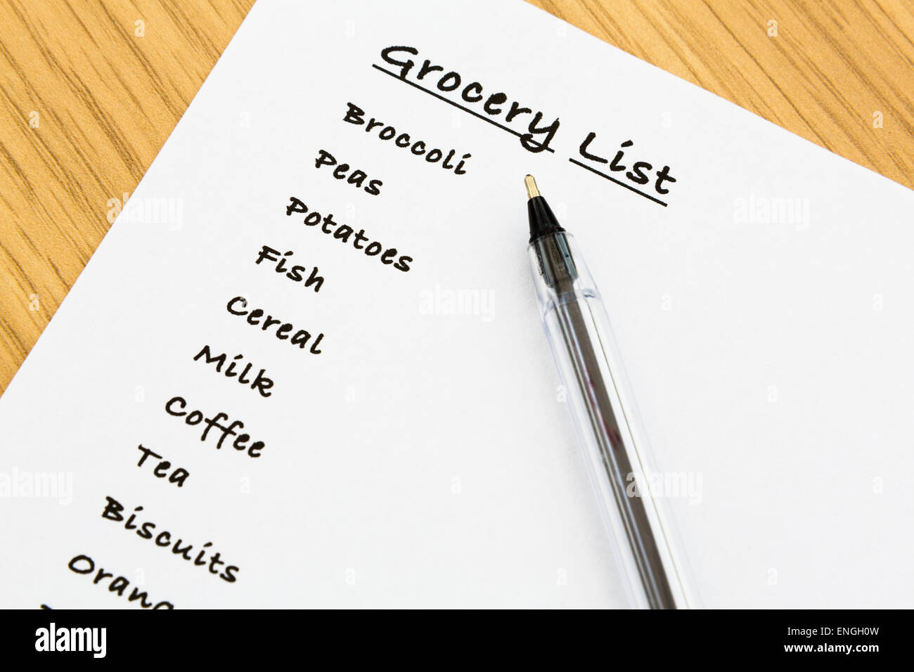Top down of a shopping list for groceries to buy written on a white piece of note paper with a black ballpoint pen. - Stock Image