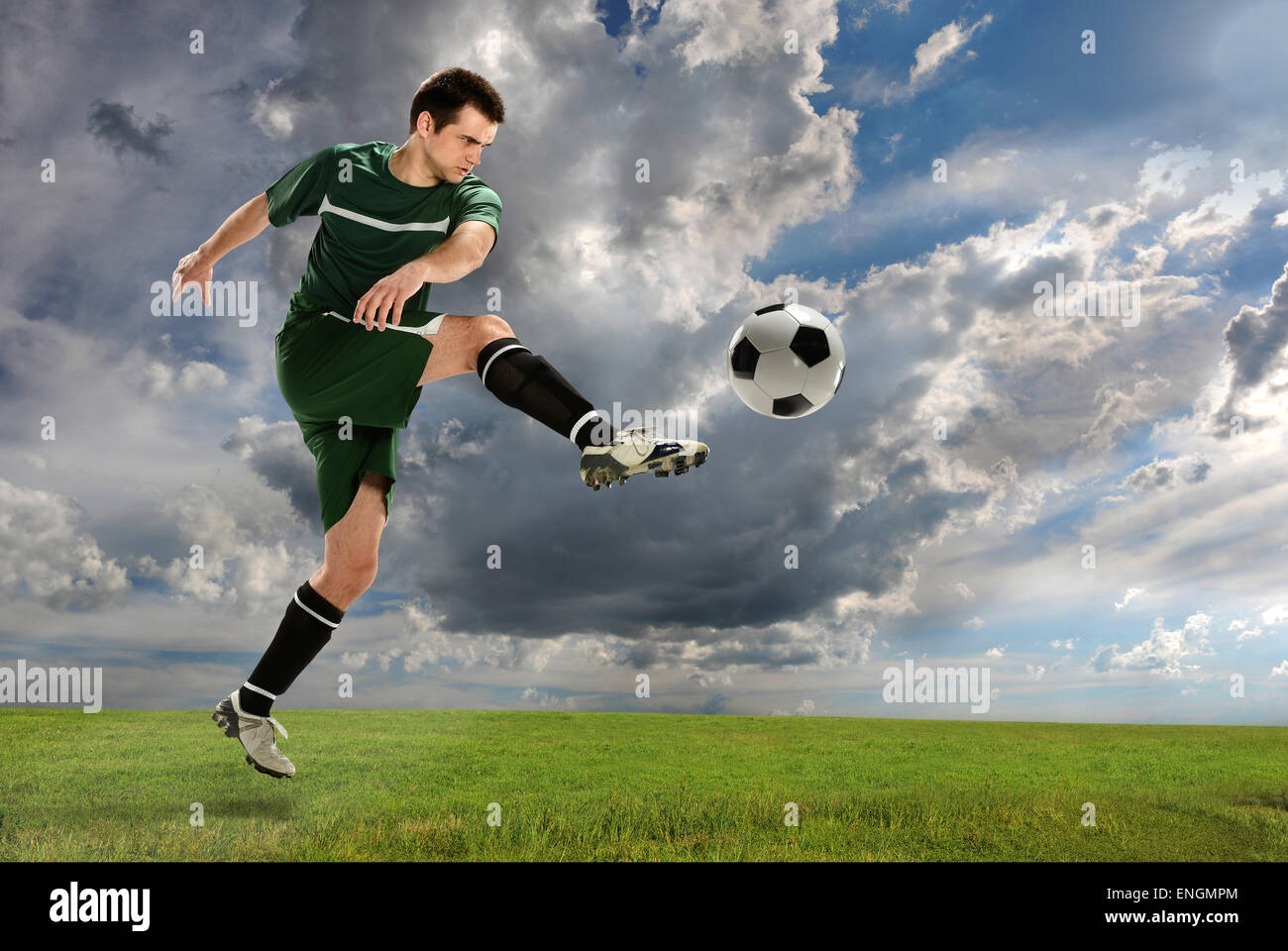 Young soccer player kicking ball outdoors - Stock Image